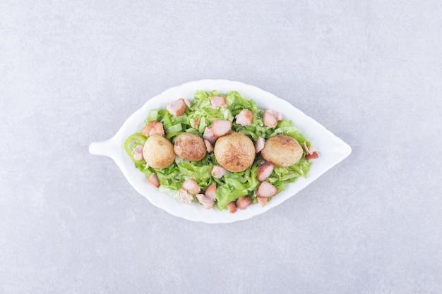 Plasterki smażone kiełbaski i sałata w białej misce.