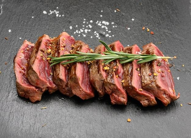 Plasterki smażony stek wołowy nowojorski rostbef na czarnej powierzchni z przyprawami, stopień wysmażenia rzadki, z bliska