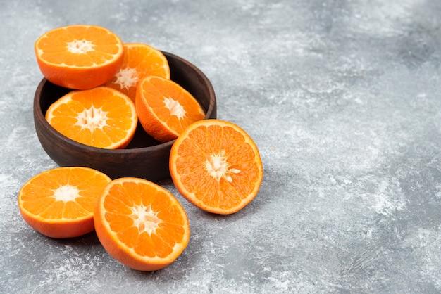 Plasterki soczyste, świeże pomarańczowe owoce w drewnianej misce.