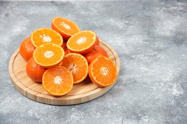 Plasterki soczyste, świeże, pomarańczowe owoce w drewnianej tablicy.