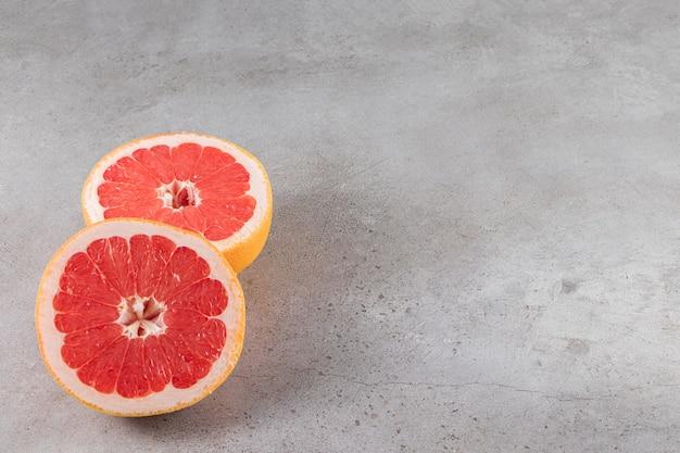 Plasterki soczystego, dojrzałego grejpfruta umieszczonego na kamiennym stole.