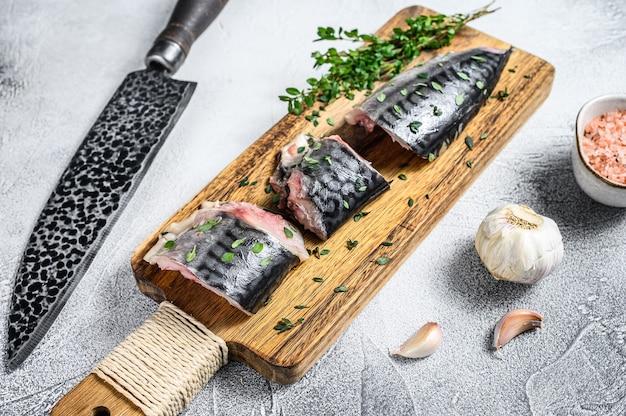 Plasterki solona ryba makrela na drewnianej desce do krojenia. białe tło. widok z góry.