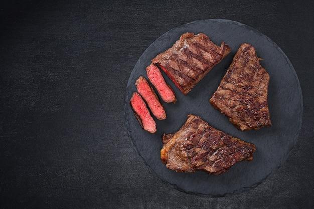 Plasterki średnio rzadki grillowany stek na desce do krojenia z rozmarynem i przyprawami