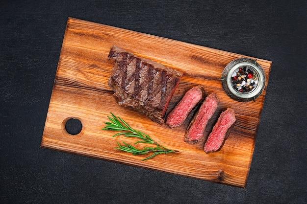 Plasterki średnio wysmażony grillowany stek na desce do krojenia