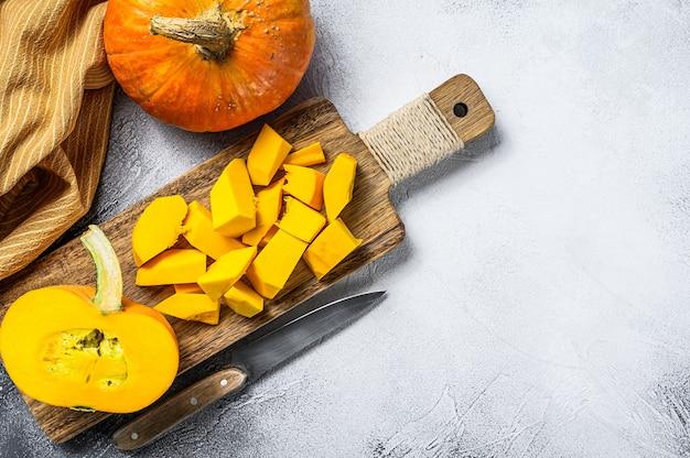 Plasterki surowej dyni pomarańczowy na desce do krojenia. białe tło
