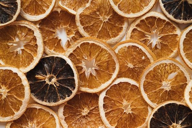 Plasterki suszonych pomarańczy. surowe owoce cytrusowe w tle. widok z góry na płasko.