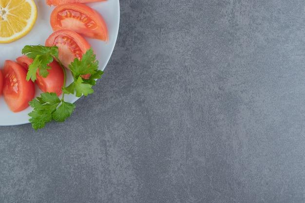 Plasterki świeże pomidory i pietruszka na białym talerzu.