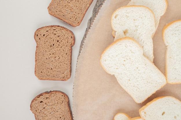 Plasterki świeżego białego i brązowego chleba na drewnianej tablicy