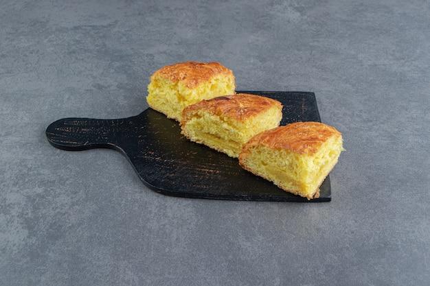 Plasterki świeżego ciasta na ciemnej desce.