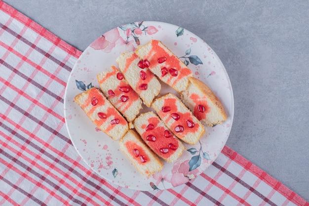 Plasterki świeżego ciasta na talerzu z nasionami granatu