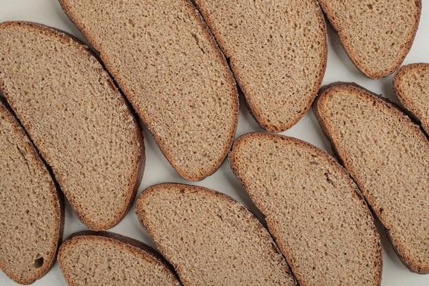 Plasterki świeżego ciemnego chleba na białym tle. wysokiej jakości zdjęcie
