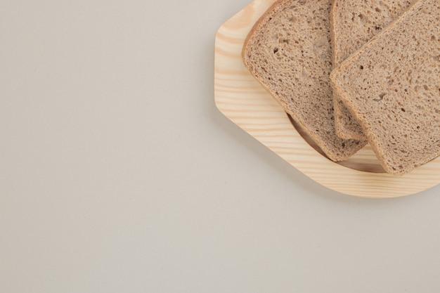 Plasterki świeżego ciemnego chleba na drewnianej tablicy