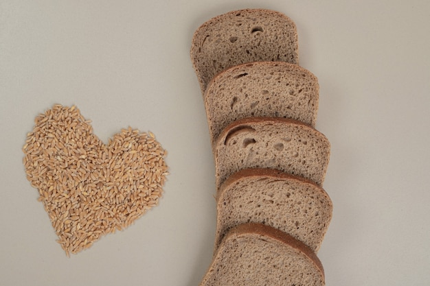 Plasterki świeżego ciemnego chleba z ziarnami owsa na białej powierzchni