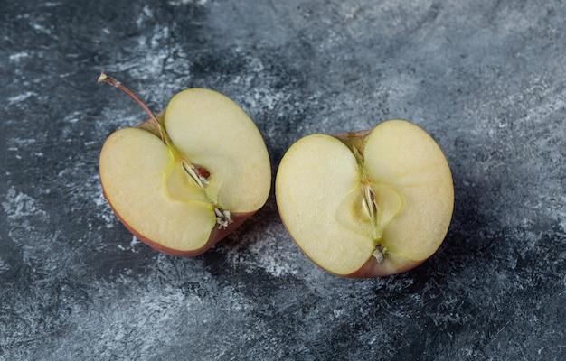 Plasterki świeżego czerwonego jabłka na marmurowym tle.