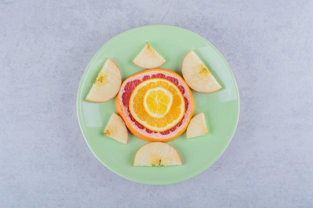 Plasterki świeżego grejpfruta, pomarańczy, cytryny i jabłka na zielonym talerzu.