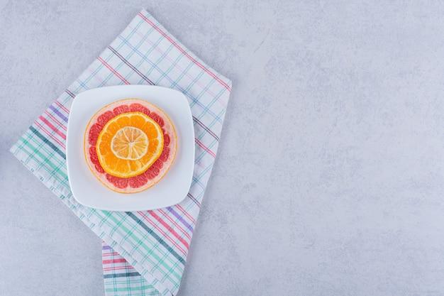 Plasterki świeżego grejpfruta, pomarańczy i cytryny na białym talerzu.