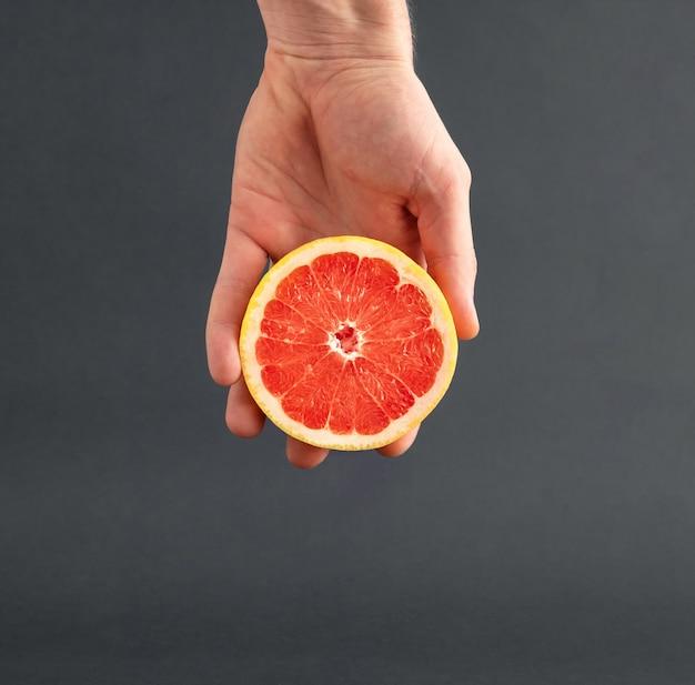Plasterki świeżego grejpfruta w dłoni mężczyzny.