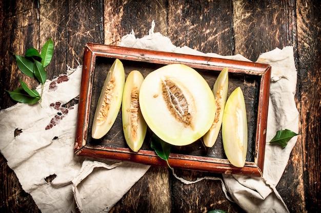 Plasterki świeżego melona. na drewnianym tle.