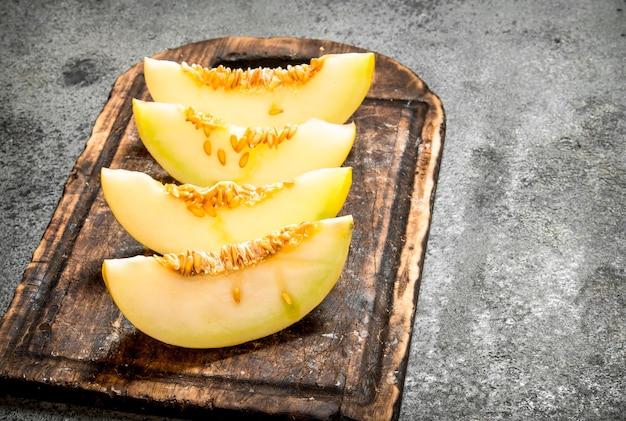 Plasterki świeżego melona na starej desce.