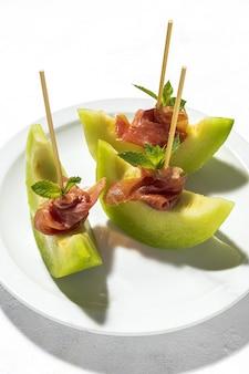 Plasterki świeżego melona z szynką ze światłem słonecznym na kolorowych tłach. koncepcja hiszpańskiego jedzenia