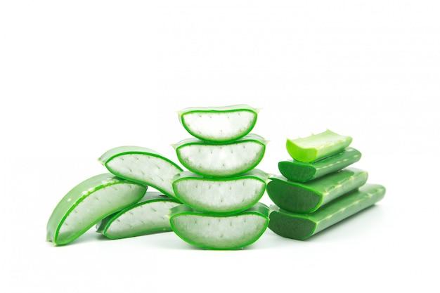 Plasterki świeżej rośliny aloe vera ułożone i łodygi aloe vera lub liście z kroplami wody izolować na białym tle.