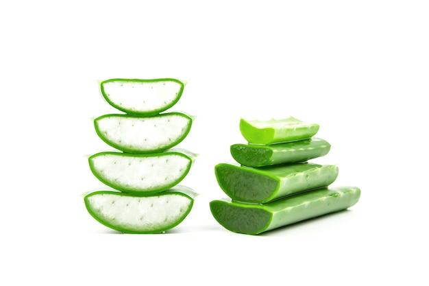 Plasterki świeżej rośliny aloesu ułożone w stos i łodyga aloesu lub liście z kroplami wody izolują na białym tle
