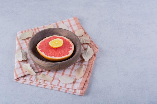 Plasterki świeżych dojrzałych grejpfrutów i cytryny w drewnianej misce.