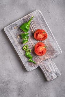 Plasterki świeżych dojrzałych pomidorów z ostrą papryką chili na starej drewnianej desce do krojenia, beton z kamienia