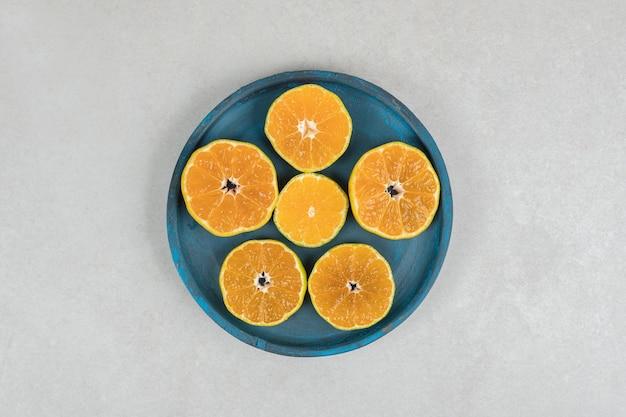 Plasterki świeżych mandarynek na niebieskim talerzu