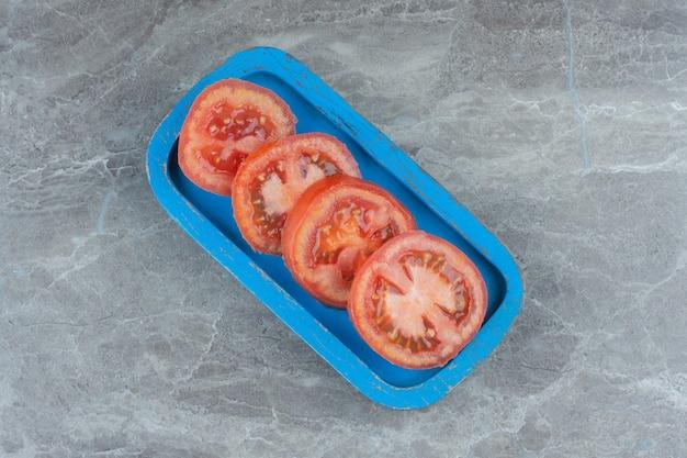Plasterki świeżych organicznych pomidorów na niebieskiej desce.
