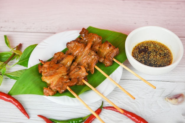 Plasterki szaszłyka wieprzowego wbija grillowanego liścia banana na białym talerzu z sosem chili czosnkiem - wieprzowina z grilla tajska azjatycka żywność uliczna