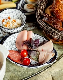 Plasterki szynki i kiełbasy z koszem chleba