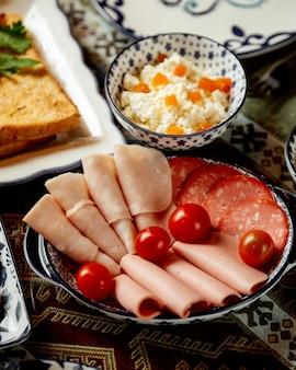 Plasterki szynki i kiełbasy z pomidorami