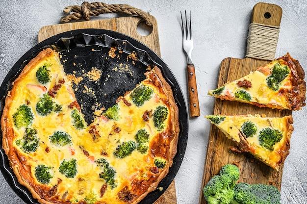 Plasterki tarty z łososiem, brokułami i śmietaną na drewnianej desce do krojenia