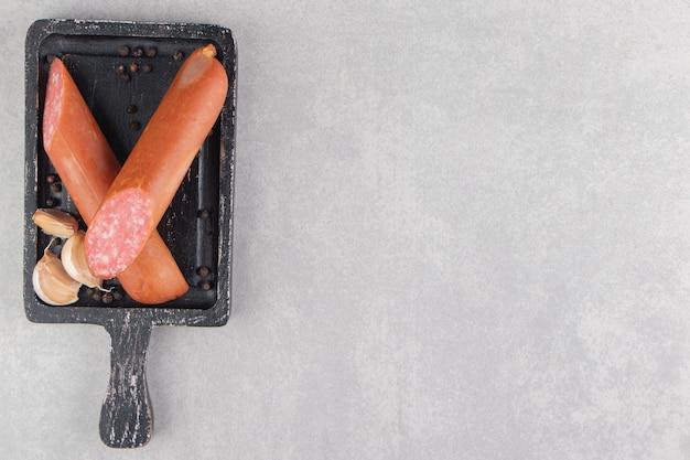 Plasterki wędzone kiełbaski i czosnek na czarnej desce.