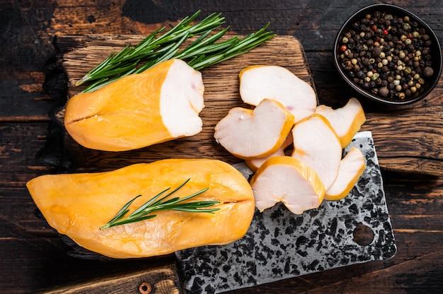 Plasterki wędzonego mięsa z piersi kurczaka na desce rzeźniczej. ciemne drewniane tło. widok z góry.
