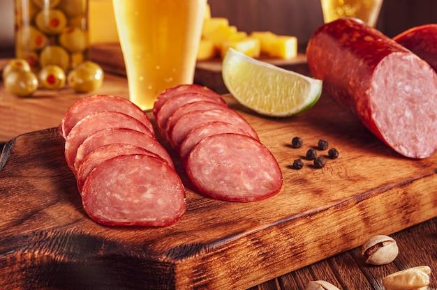 Plasterki wędzonego salami na desce do krojenia ze szklanką piwa, kawałkami sera, oliwkami i pistacjami
