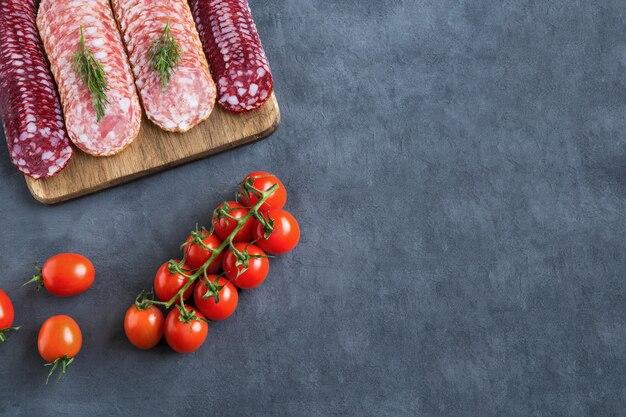 Plasterki wędzonych kiełbasek na deska do krojenia z pomidorami cherry płasko leżał na szarym tle z miejsca na kopię