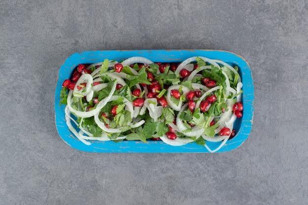 Plasterki zieleni, cebuli i nasion granatu na niebieskim talerzu. zdjęcie wysokiej jakości