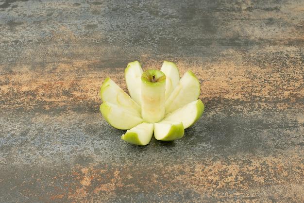 Plasterki zielonego jabłka na powierzchni marmuru.