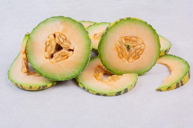 Plasterki zielonego melona na białym tle.
