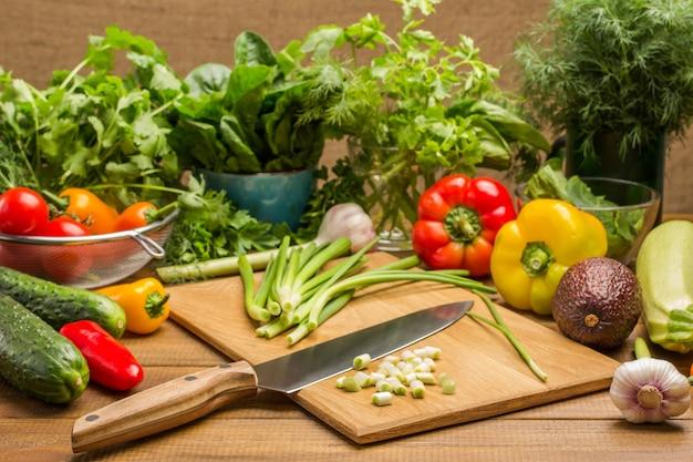 Plasterki zielonej cebuli i nóż kuchenny na desce do krojenia. warzywa i zielenie na stole. drewniane tło.
