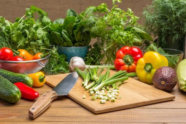 Plasterki zielonej cebuli, nóż kuchenny na desce do krojenia. warzywa i koperek, liście szpinaku i kolendra na stole. drewniane tło.