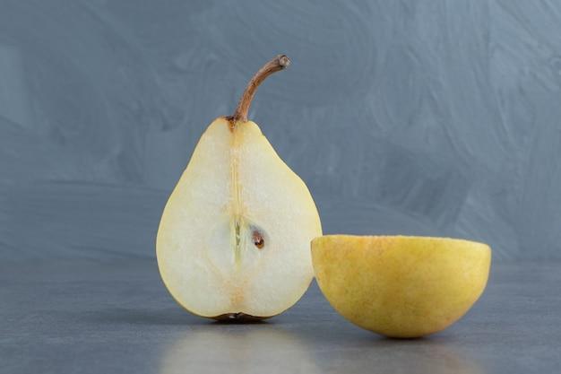 Plasterki żółtej gruszki na białym tle na szarej powierzchni