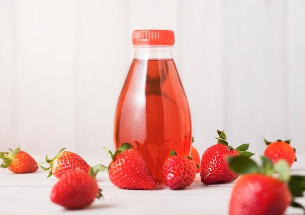 Plastikowa butelka jagoda soku soku napój na drewnianym tle z świeżymi truskawkami