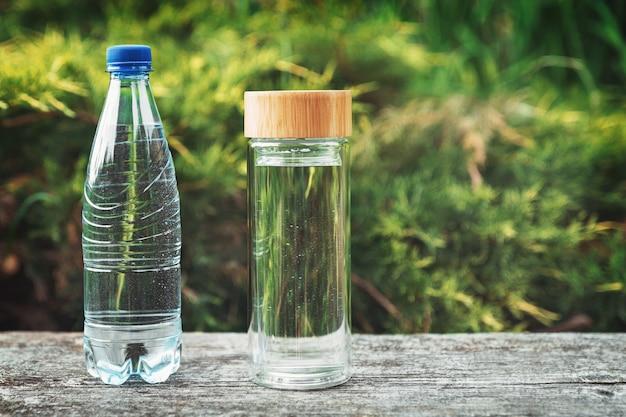 Plastikowa butelka na wodę i stylowa szklana butelka wielokrotnego użytku o niewyraźnej naturze