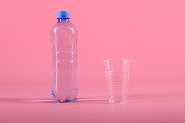 Plastikowa butelka plastikowy kubek nadal zdrowej wody na białym tle na różowym tle. makieta