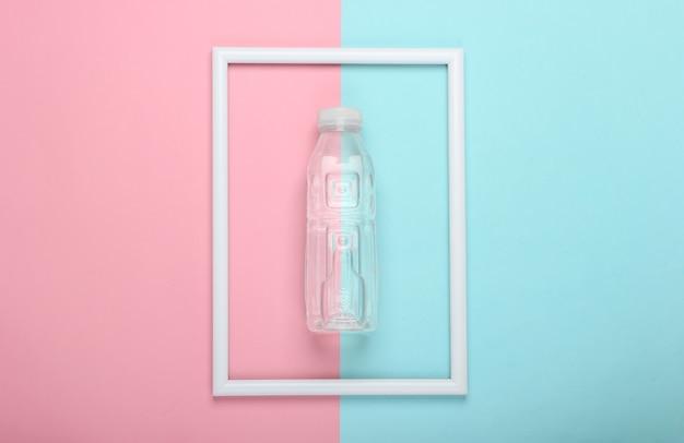 Plastikowa butelka wody na różowo-niebieskiej pastelowej powierzchni z białą ramką