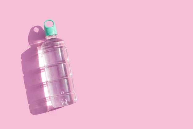 Plastikowa butelka wody na różowym tle.