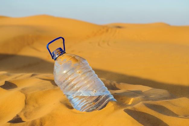 Plastikowa butelka wody w piasku pustyni z błękitnym niebem